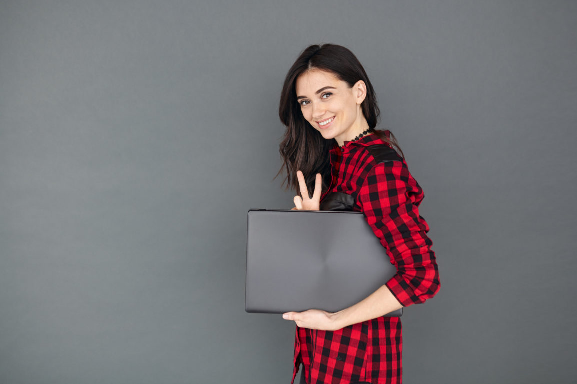 young brunette woman holding laptop over grey background